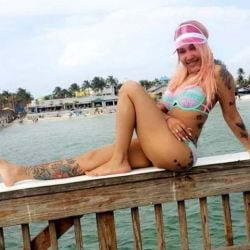 A girl sitting on a dock on the water in Fort Myers Beach.