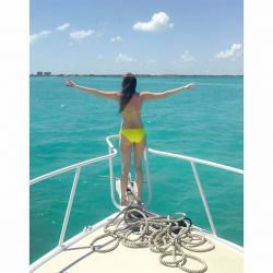 A photo of a girl standing on bow of a boat with outstretched hands in Grand Cayman
