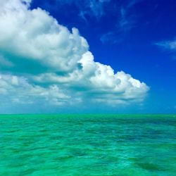 A photo of a thick band of white clouds rolling over the waters of Islamorada in the Florida Keys.