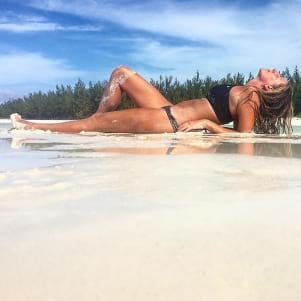 Girl laying on sand in the Berry Islands, Bahamas